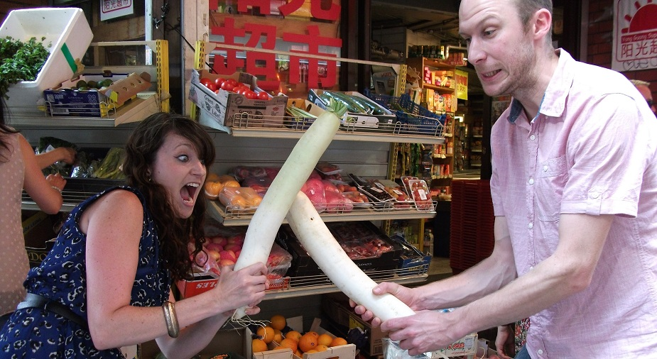 Two people fighting with vegetables on a Chinatown Treasure Hunt.